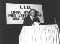 """1° congresso nazionale della LID. Antonio Baslini parla da una tribuna alle sue spalle banner: """"""""LID lega italiana per l'istituzione del divorzio"""""""" (B"""