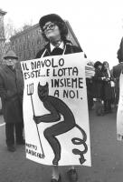 """""""Valeria Ferro durante una marcia contro il concordato, tiene al collo un cartello: """"""""il diavolo esiste e lotta insieme a noi. PR""""""""  (BN)"""""""