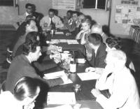 assemblea intorno ad un tavolo. Vista dall'alto di tutti i riuniti con De Matteis a capotavola. (BN)
