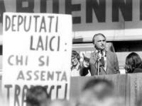 """Comizio di Pannella davanti al cinema Adriano. Accanto a Pannella, dinanzi a un microfono, sul palco, si legge il cartello: """"Deputati laici: chi si as"""