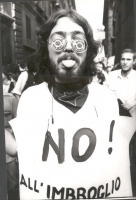 """Manifestazione antinucleare. Un manifestante, con le lenti degli occhiali coperte da un adesivo su cui è scritto: """"Nucleaire? Non merci"""", e al collo u"""