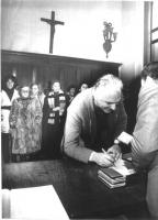 Marco Pannella è chino a firmare un atto ufficiale. (?) Sulla parete di fondo, alcune signore assistono alla scena. Bianco e nero. 2 copie + negativo