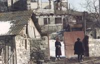 Scena di guerra. Una donna sulla soglia di una casa semidistrutta.