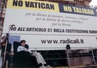 """Comizio anticlericale davanti a porta Pia. Luca Coscioni, seduto davanti al banner, """"No Vatican no Taliban""""."""