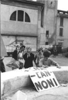 """3a marcia antimilitarista Milano-Vicenza. Su una fontana è esposto il cartello: """"+ case - cannoni""""."""