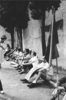 """3a marcia antimilitarista Milano-Vicenza. Marciatori seduti a terra. In primo piano, Angiolo Bandinelli, con il cartello: """"Disarmo unilaterale - Parti"""