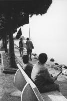 3a marcia antimilitarista Milano-Vicenza. Sul lungolago, due donne sedute in panchina si voltano verso due marciatori, uno dei quali porta il cartello