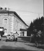 """3a marcia antimilitarista Milano-Vicenza. Di fronte alla caserma, un marciatore indossa il cartello: """"Esercito scuola di assassini""""."""