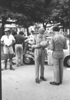 """3a marcia antimilitarista Milano-Vicenza. In primo piano, due militari leggono volantini antimilitaristi. Sullo sfondo il cartello: """"Mio figlio non uc"""