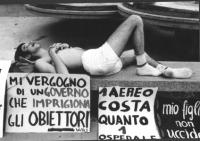 """3a marcia antimilitarista Milano-Vicenza.Tratta: San Bonifacio-Arzignano. Marciatore a riposo. Cartelli: """"Mi vergogno di un governo che imprigiona gli"""