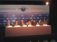 """""""Cooperando per la democrazia - Terza conferenza ministeriale per la Comunità delle Democrazie"""". Tavolo dei conferenzieri, con banner."""